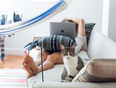 barefoot man lays on couch with his cat