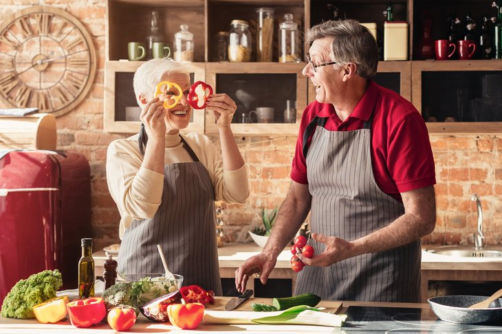 A senior couple cuts vegetables for a salad while cooking a meal in their kitchen