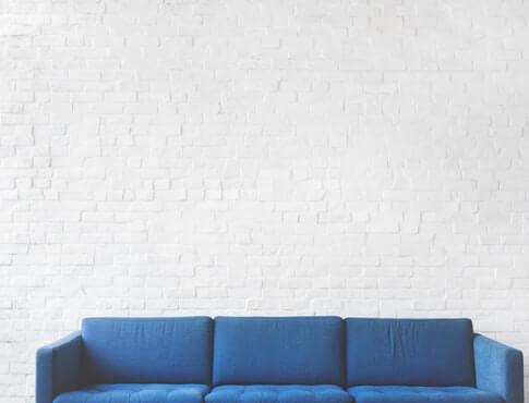 blue couch against plain white brick wall