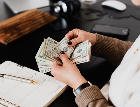 Woman counting cash with a planner on her desk