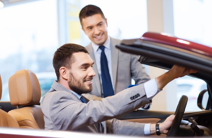 A car shopper looks at a convertible in an auto dealership showroom with a salesman