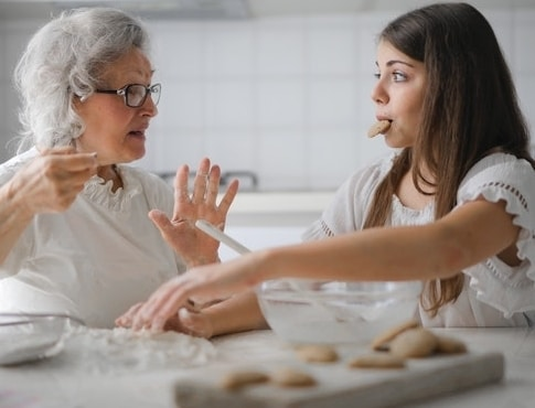 Older woman talking to girl with cookie in mouth